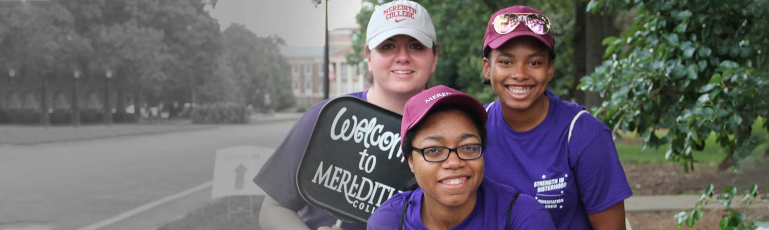 Three Meredith students holding sign that says welcome to Meredith