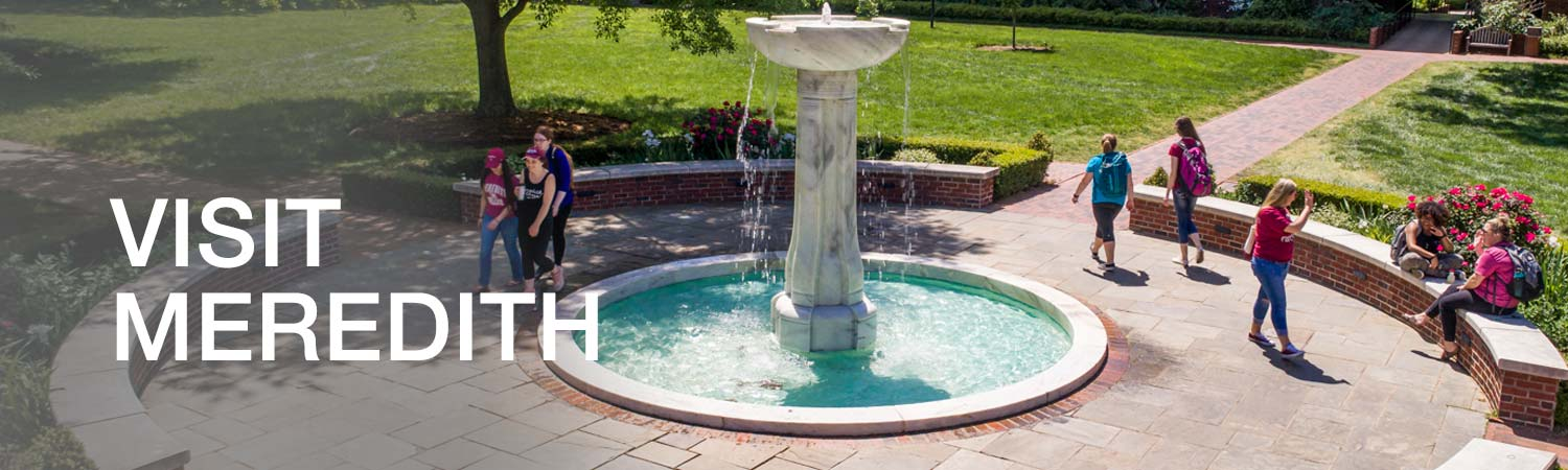 students walking around a fountain
