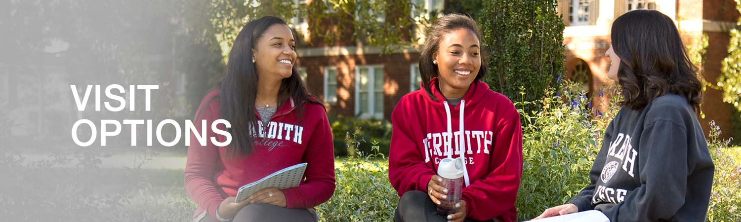 Three female students sitting outside on campus