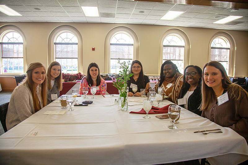a group of female students sitting at a table at the Brenda Hughes event