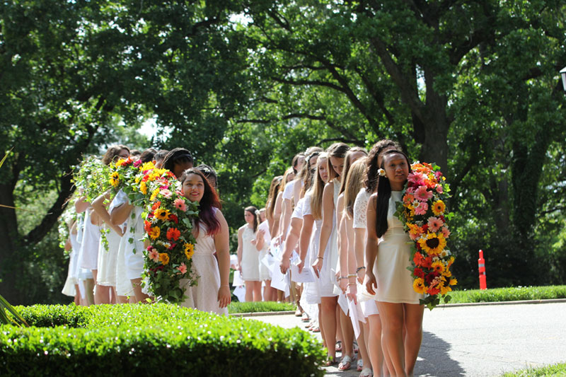 Sophomores dressed in white and holding the daisy chains