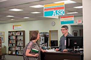 A student at the front desk of the library talking to a librarian.