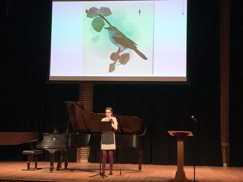 Student playing the clarinet during a presentation, a photo of a bird is shown on a screen behind the student