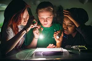 Three students in a dark room holding flashlights reading clues.