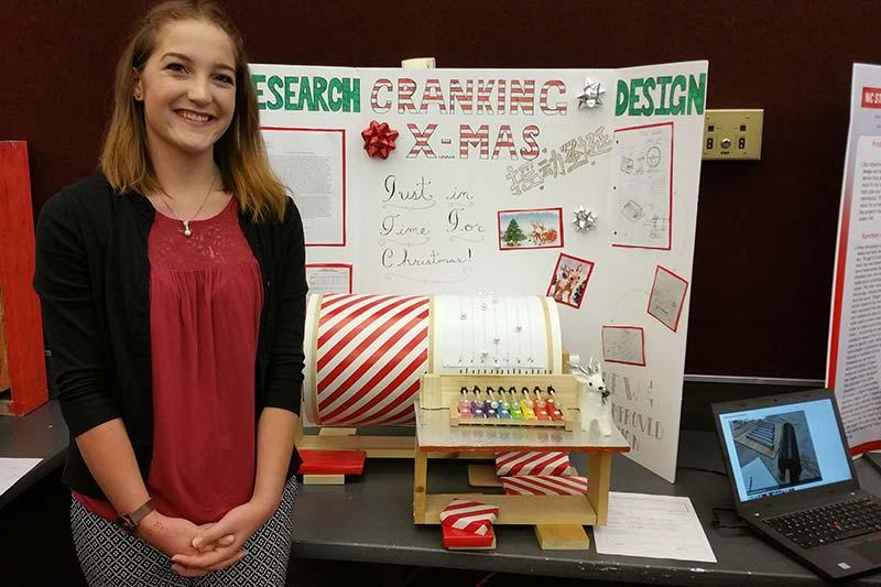 Rebecca Kline in front of Cranking Christmas music maker