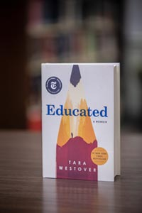 The Book Educated - sitting up on a desk with blurry bookshelf in background