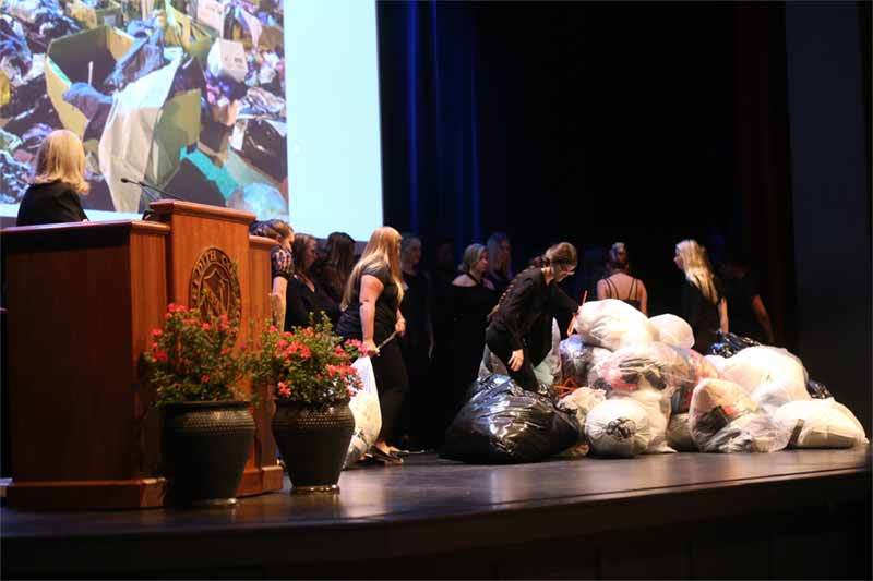 Ellis said that an average of 70 pounds of textiles are thrown away annually by each American. She had 28 current students and one future student bring trash bags full of textiles onto the stage to help the audience visualize one ton of fabric waste