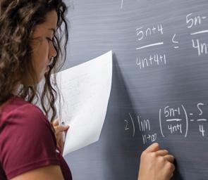Girl working on math problem at blackboard