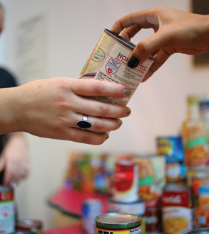 A can of food being handed from one student to the other at food drive