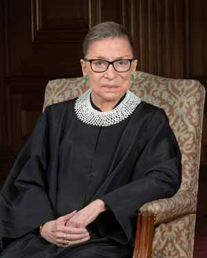 Supreme Court Justice Ruth Bader Ginsburg seated in chair looking towards camera