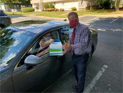 Lennie Barton Delivering package to woman in car