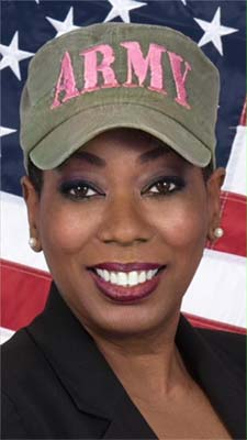 Sandra Robinson in Army hat posing in front of flag