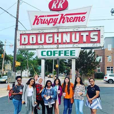 international Students standing side by side in front of Krispy Kreme Doughnut Sign