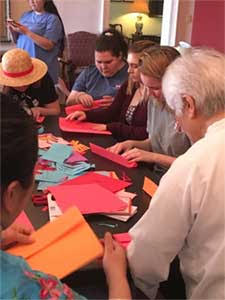 a group of people sitting at a table creating origami