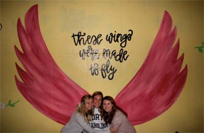 Students posing in front of Painting of Wings that says These wings are made to fly