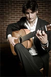 Edward Stephenson in a grey sport jacket and white shirt, sitting cross legged playing guitar
