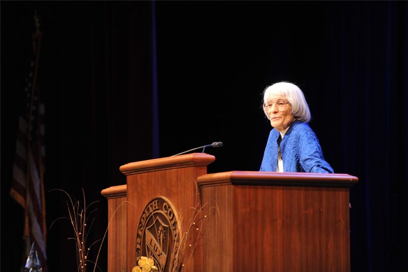 Bernice Sandler speaks at Meredith College behind a lectern with the College seal on it