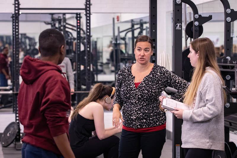 Students gather with a professor in the fitness center