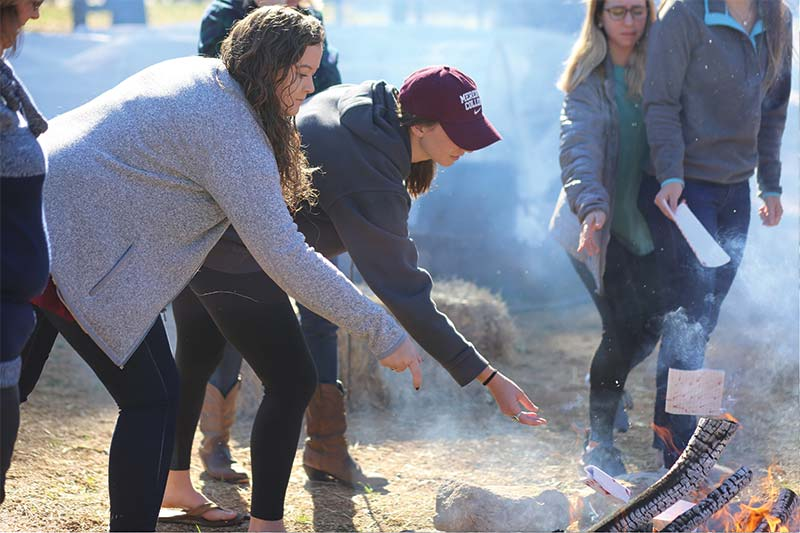 Students gathered around a fire and burning notes they have written