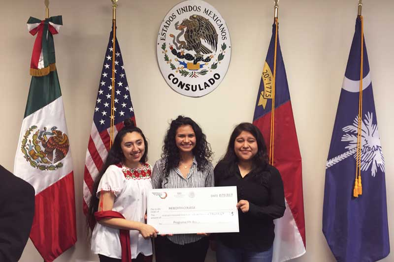 Three Meredith students in front of Mexican, U.S., N.C. and S.C. flags, holding a presentation check representing scholarship funds