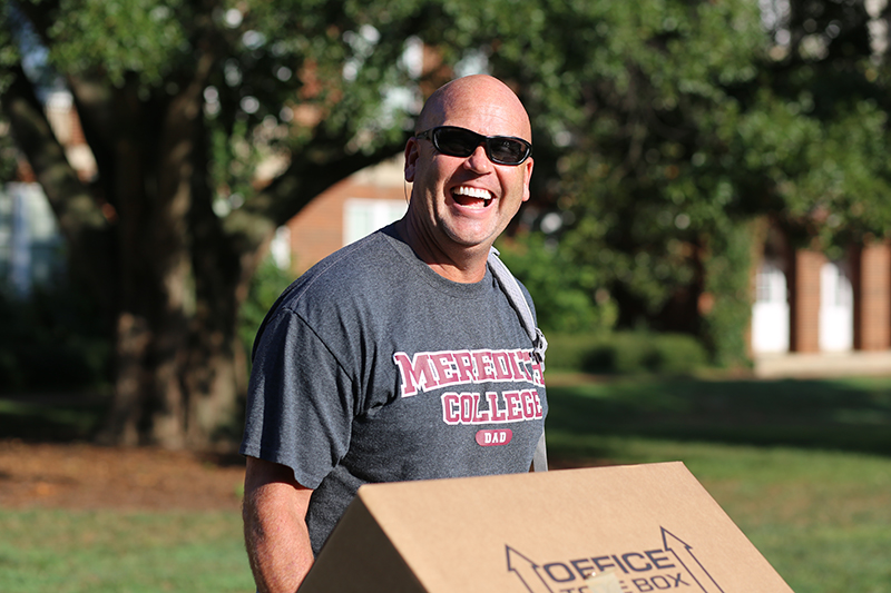 man moving boxes wearing a Meredith college dad shirt