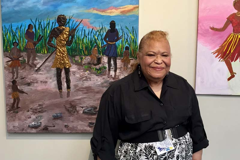 Senior Wings student Margaret Gaskin-Tuell standing in front of one of her paintings during her art exhibition