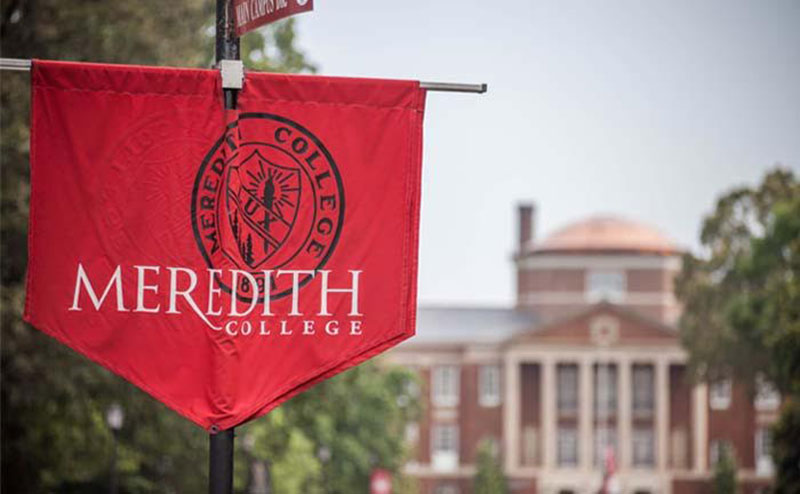 A Meredith College banner in the foreground with Johnson Hall in the background.