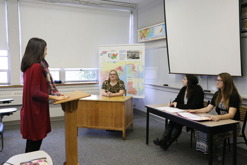 A student presents to her professor and two classmates during Moot Court class