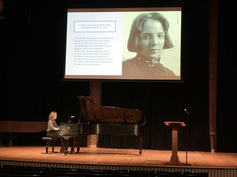 Student plays piano during a presentation about composer Sophie Eckhardt-Gramatte, whose photo is shown on a screen above the piano