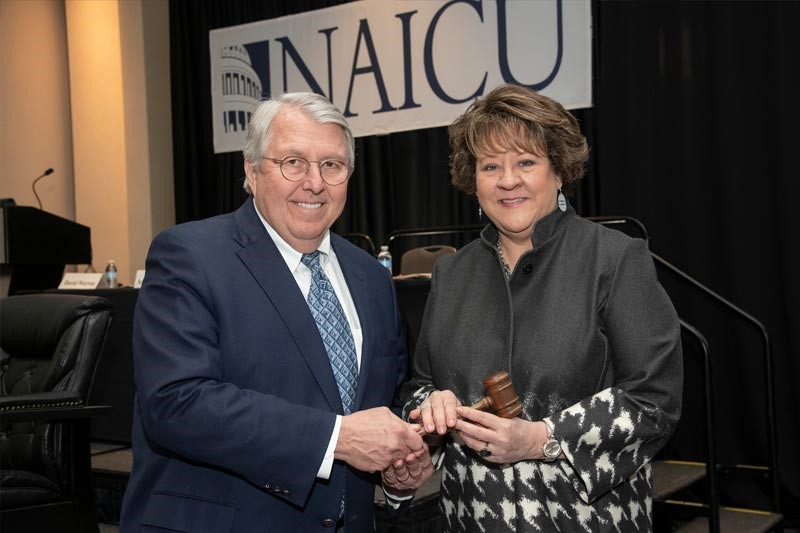 Photo shows President Jo Allen accepting the board chair's gavel from previous board chair Andrew K. Benton