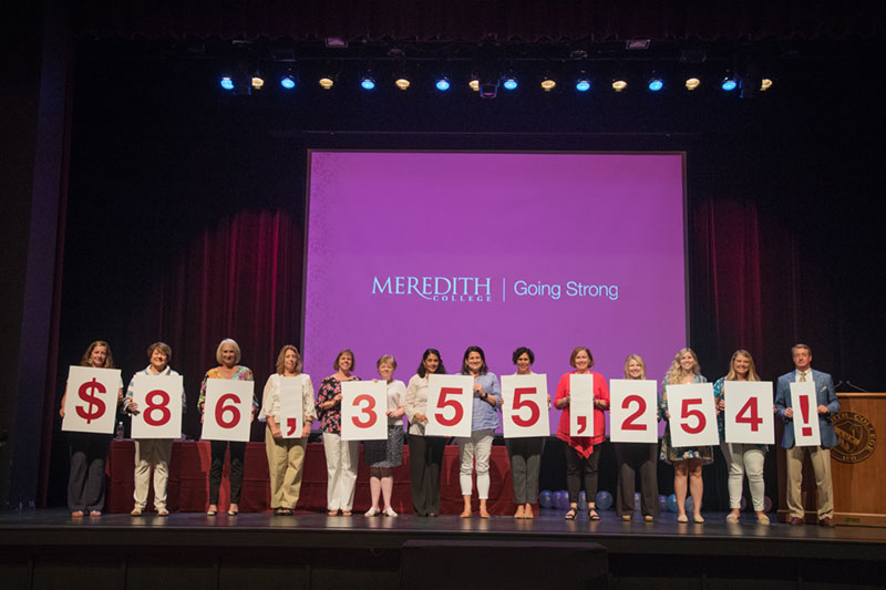 President Allen and Staff members holding signs that show a total of $86,355,254!