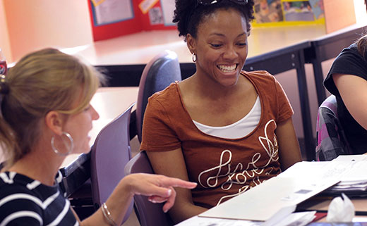Student smiling and learning in a classroom