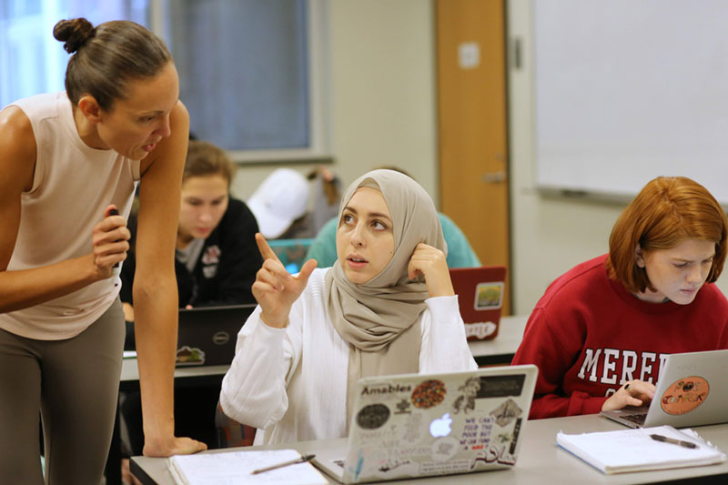 student talking with professor in front of an open laptop