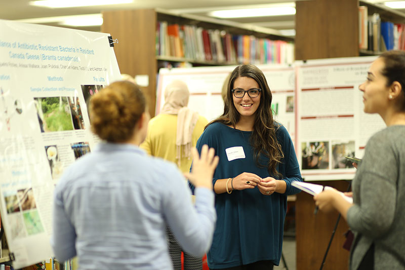 A Meredith student standing in front of a poster presenting her research to another student