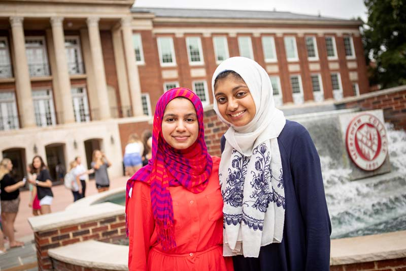 Two Students wearing colorful hijabs smiling in front of Beam Fountain