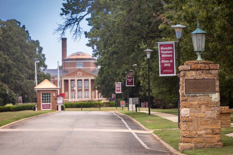 Front Gate entrance to college with stone column and red flags lining entrance with Johnson Hall visible in distance