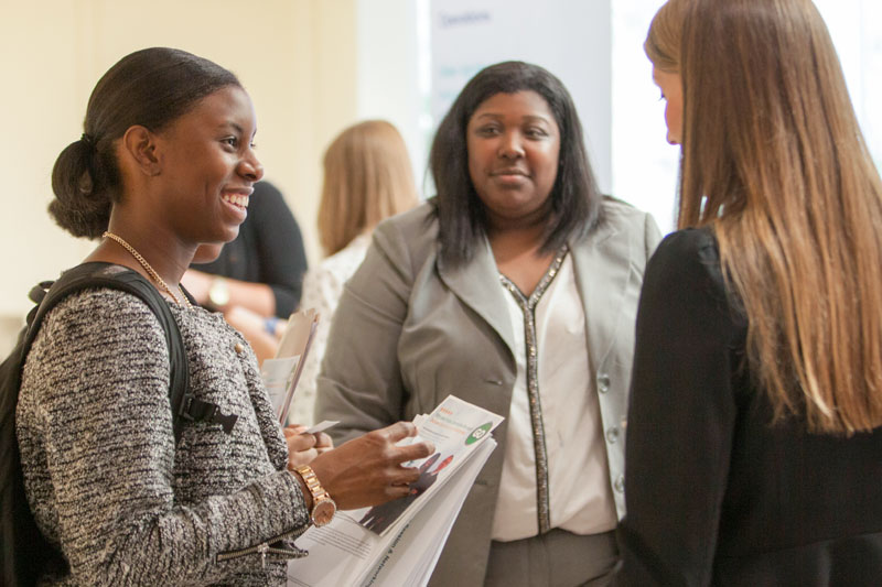 Three women talk at networking event