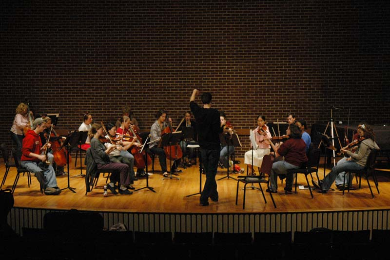 About 15 Orchestra Students practicing instruments on Carswell Auditorium stage
