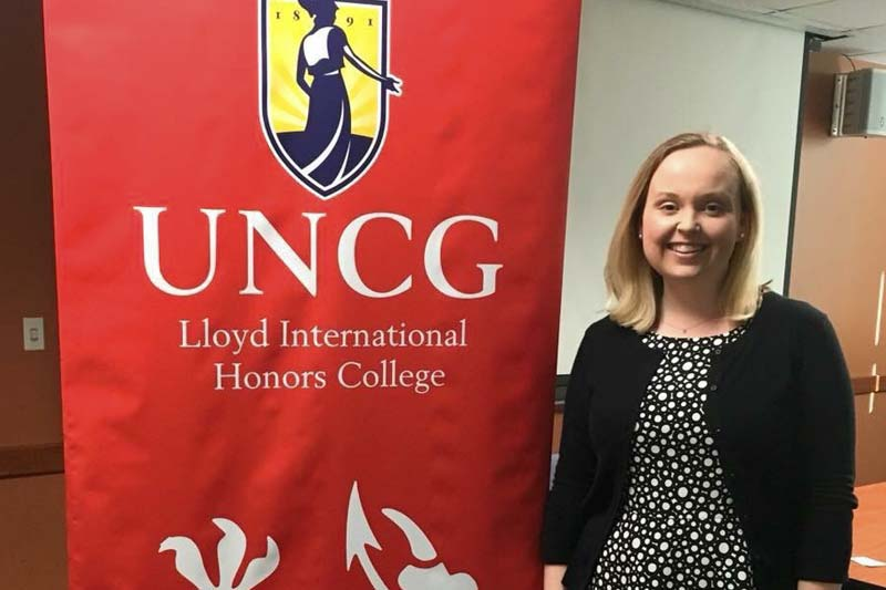 Photo of Catherine Koontz in front of a banner that says UNCG Lloyd International Honors College