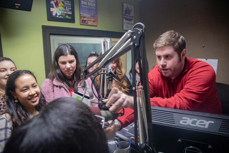 radio host showing students behind the scenes at rec