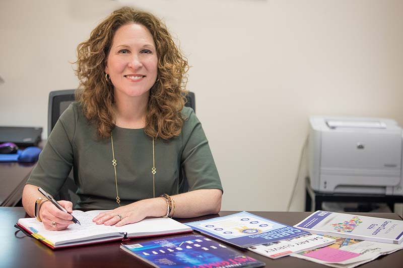 Dana Sumner sitting at her desk with career planning material.