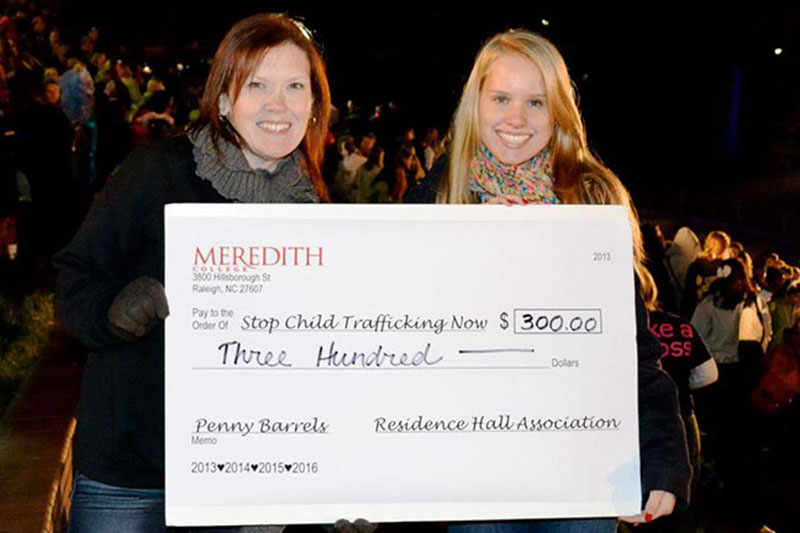 Two women holding a check