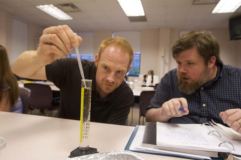 Male Graduate Students Measuring Liquid in Beaker