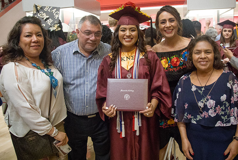 Commencement Graduate and Family posing with diploma