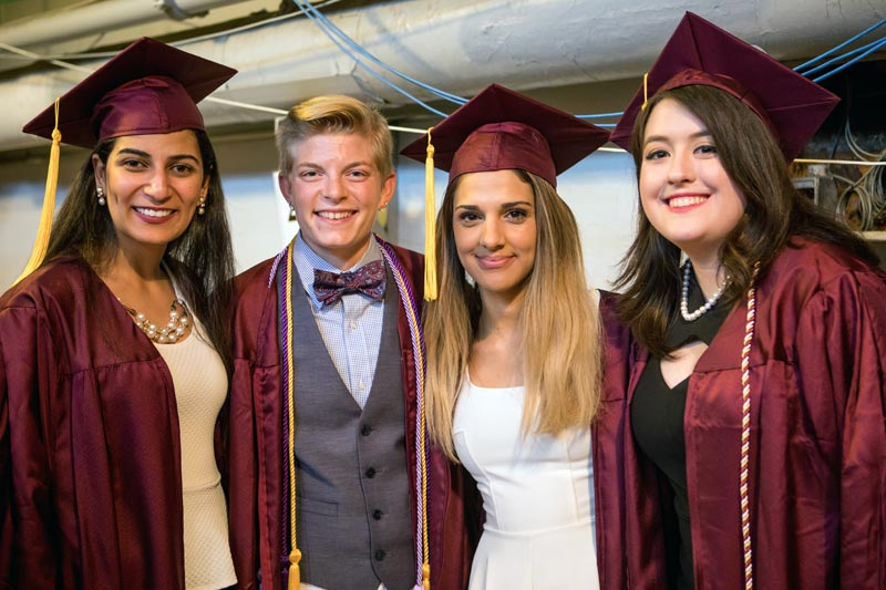 Four Students at Commencement dressed in regalia