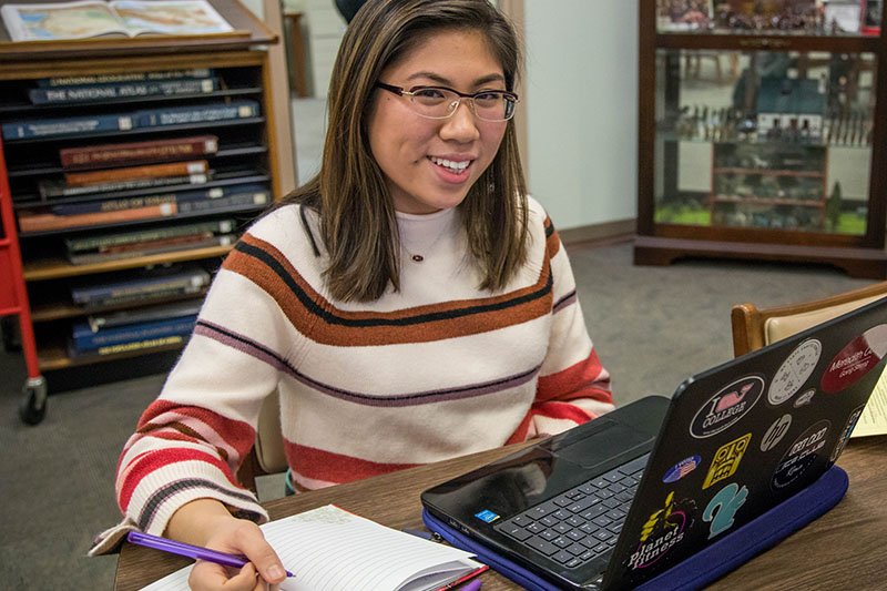 A student working on her laptop in the library