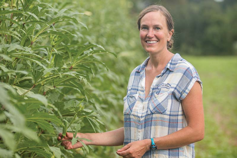 Image of woman in front of crops.
