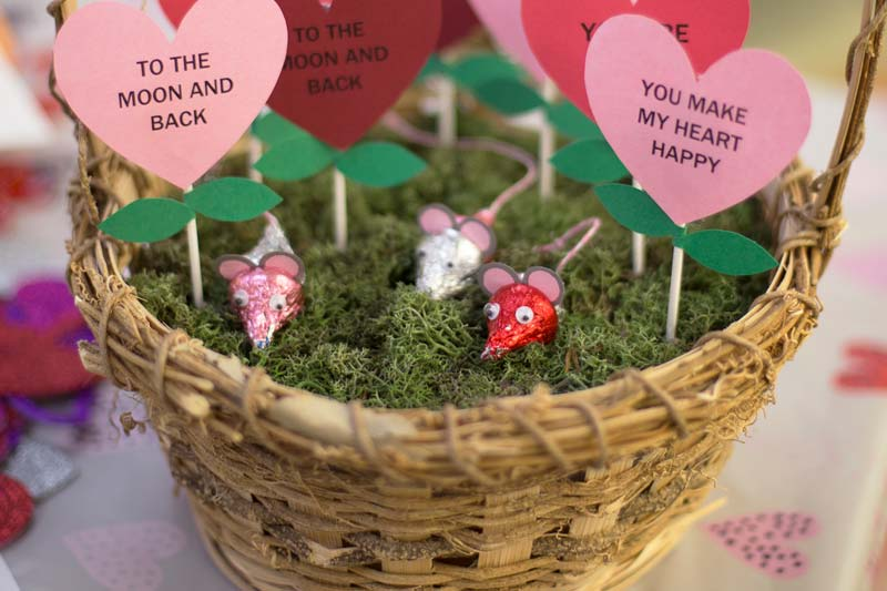 Basket with construction paper hearts with Valentines messages written on them