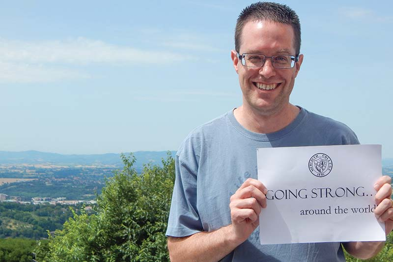 Mark O'Dekirk holding a Going Strong around the world sign.