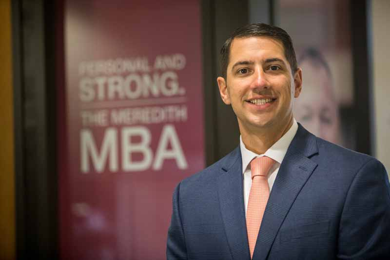 MBA alumnus Matthew Evans in front of sign that says Personal and Strong. The Meredith MBA